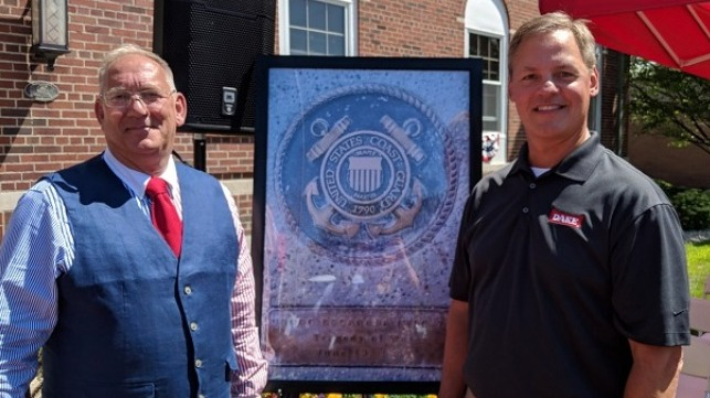 Mitch Mittlestadt and Mike Smith, USCG (retired) in front of the photo of the plaque at the unveiling ceremony