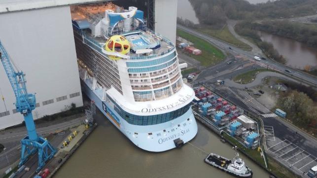 large cruise ship emerges from building hall