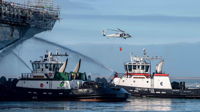 Tugs provide cooling water on the bow as firefighting efforts continue, July 15 (USN)